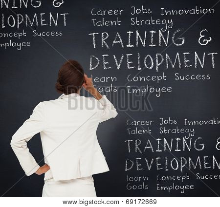 Thinking businesswoman against blackboard with business buzzwords