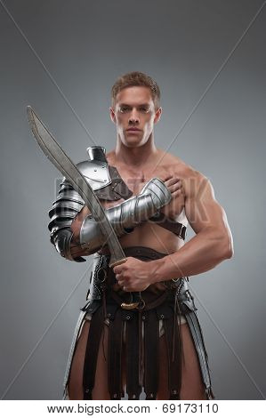 Gladiator in armour posing with sword over grey background
