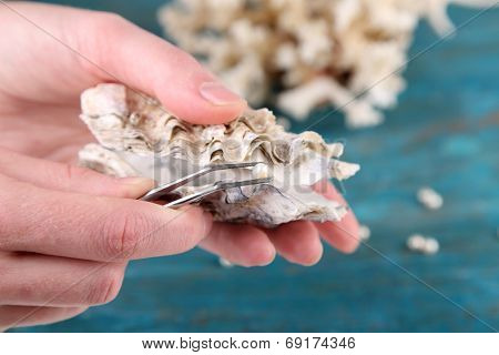 Hand with tweezers holding pearl and oyster on wooden background