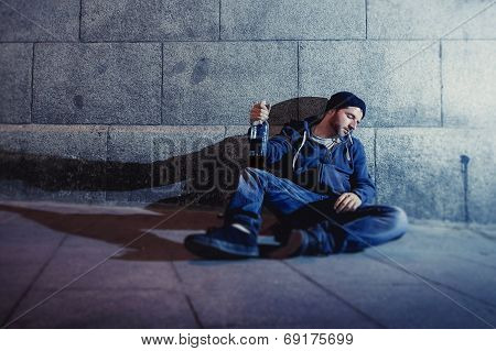 Alcoholic Grunge Man Sitting On Ground Street Corner Drinking Alcohol Bottle