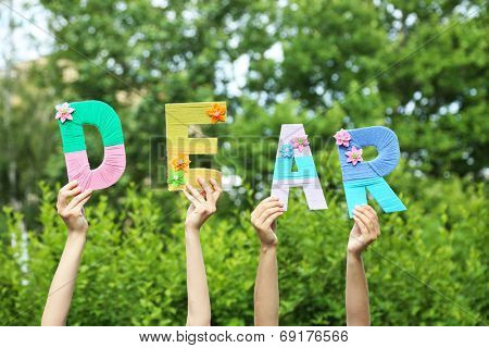 Hands holding up letters building word dear on natural background