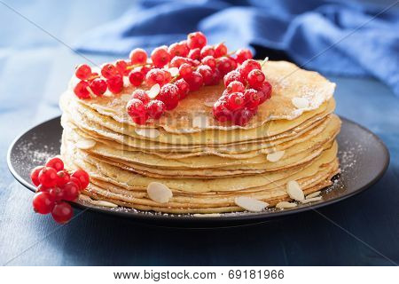 stack of pancakes with redcurrant and powder sugar