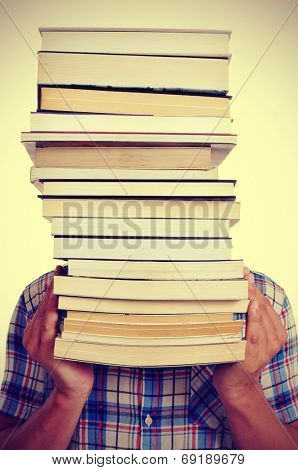 a young man holding a pile of books in front of his face, with a filter effect