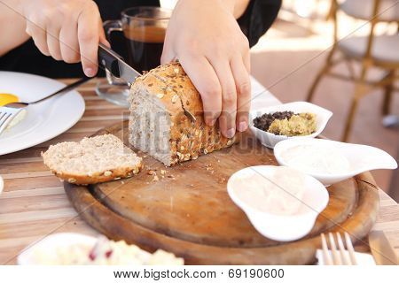woman cut the home made bread on wooden board near tapases outside cafe