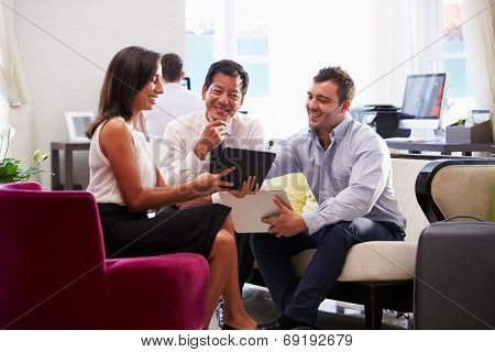 Three Businesspeople Having Meeting In Hotel Lobby