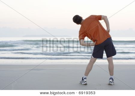 Jogger Doing Stretching On A Beach