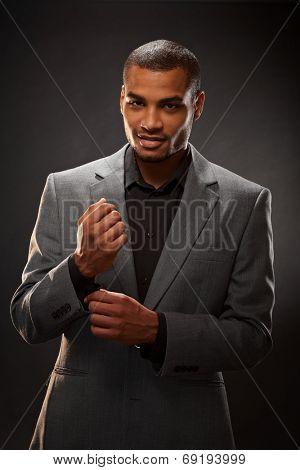 Afro-american businessman in jacket, studio photo on black background.