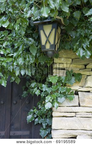 detail of a stone wall, ancient door and lantern
