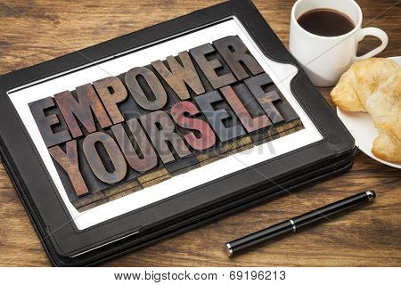 empower yourself - motivation concept - text in vintage letterpress wood type blocks stained by ink on a digital tablet with cup of coffee