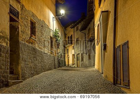 Narrow cobbled street among old houses at night in town of Barolo, Italy.