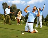 stock photo of kneeling  - Happy golfer kneeling at hole with raised fists after putting in golf ball to the hole - JPG