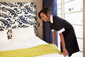 pic of maids  - Maid Tidying Hotel Room And Making Bed - JPG