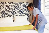 stock photo of maids  - Maid Tidying Hotel Room And Making Bed - JPG