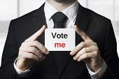 stock photo of prime-minister  - politician in black suit holding sign vote me - JPG