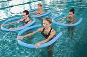 stock photo of day care center  - Fitness class doing aqua aerobics with foam rollers in swimming pool at the leisure centre - JPG
