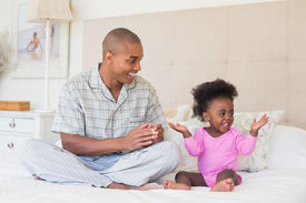 stock photo of babygro  - Happy father and baby girl sitting on bed together at home in the bedroom - JPG