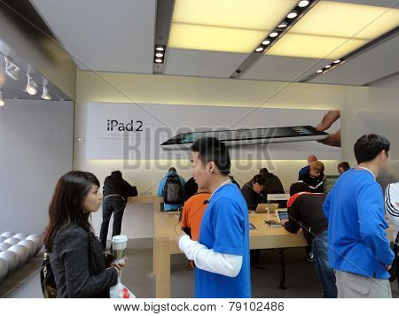 People Look At Products And Talk To Sales Reps Inside Apple Store With Ipad 2 Ad On Wall