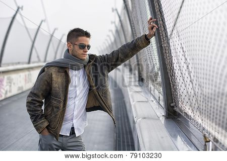 Handsome trendy man standing on a bridge, looking down