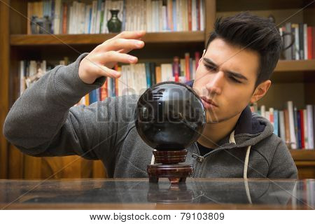 Young Man Predicting The Future By Looking Into Crystal Ball