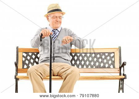 Happy senior checking the time seated on a bench isolated on white background