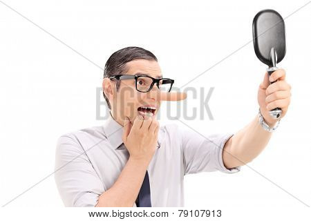 Scared man with long nose looking in a mirror isolated on white background