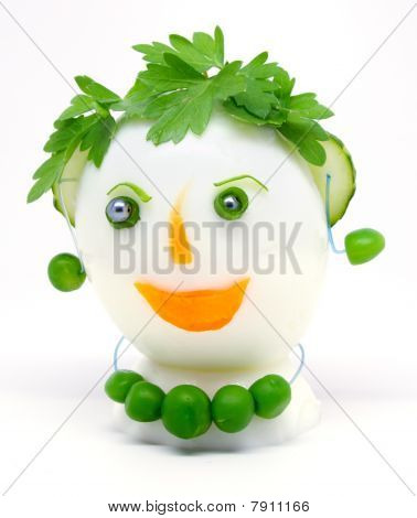Egg garnished with parsley, cucumber, carrots and green peas