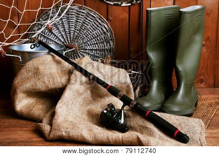 Fishing equipment on wooden wall background, indoors