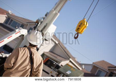 Utility Worker Navigating Remote Crane
