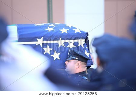 Flag-draped coffin carried outside
