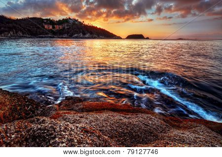 Beautiful and romantic sunset beach with distant cliffs and swirling waters