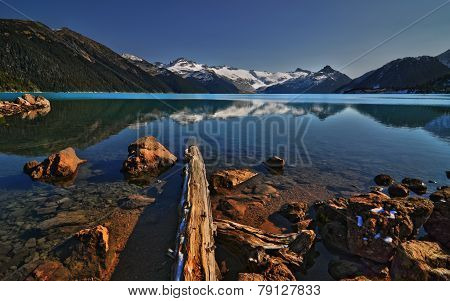 Driftwood laying in a crystal clear mountain lake