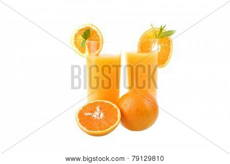 two glasses of orange juice with some oranges