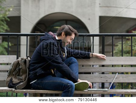 Young Man Sitting On Bench Smiling At Laptop