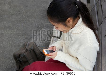 Young Woman Sending Text Message On Mobile Phone