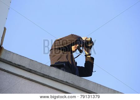 Rooftop security with binoculars
