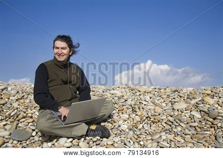 young casual man with laptop at the beach