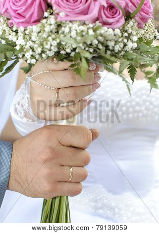 a wedding pair holds the bouquet of roses