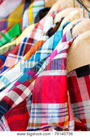 Close Up Of Colorful Checked Shirts With Hangers.