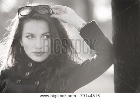 cute woman leaning on a tree and holding glasses looking away b&w