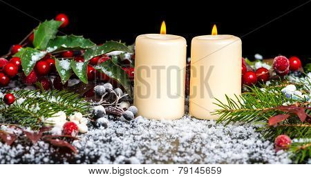 Christmas Card Of Decorated Evergreen Branches, Red Leaves, Berry With Snow And Candles, Closeup
