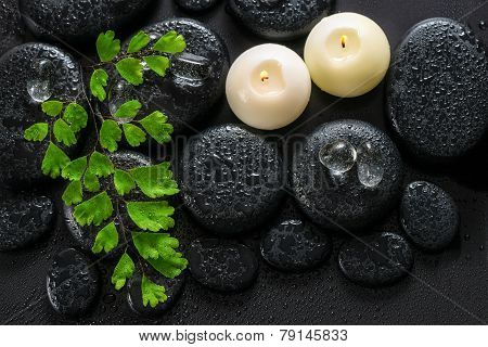 Beautiful Spa Still Life Of Green Twig Fern, Ice And Candles On Zen Basalt Stones With Dew, Closeup