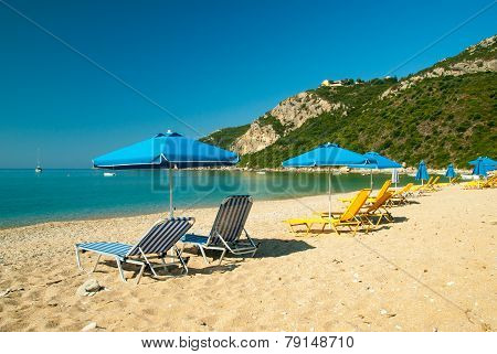 Blue And Yellow Sunbeds And Blue Umbrella On A Beautiful Beach In Corfu Island, Greece