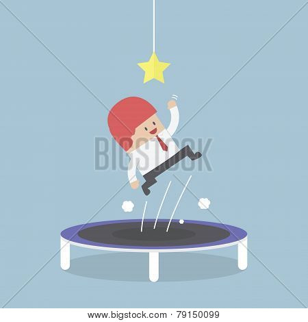 Businessman Trying To Catch The Star By Jumping On Trampoline