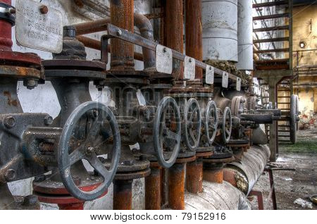 Old Pipes With Valves In A Deserted Hall