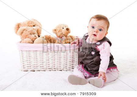 Toddler Sitting Next to Teddy Bears