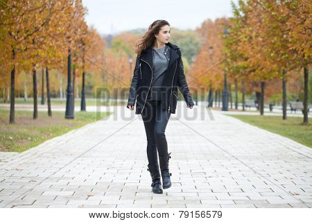 Beautiful woman in black coat walking autumn street