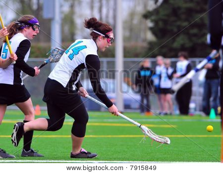 Girls Varsity Lacrosse player going for the ball