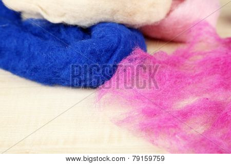 Multicolored wool for felting on wooden background