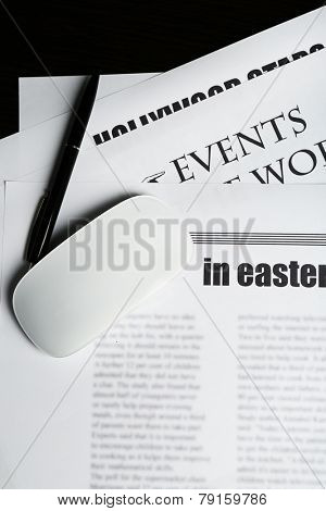 On-line news concept. Computer mouse and newspaper, close-up
