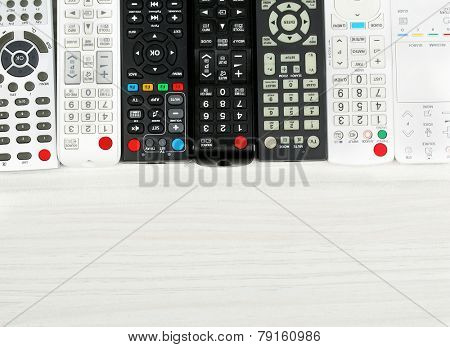 Many remote control devices on table